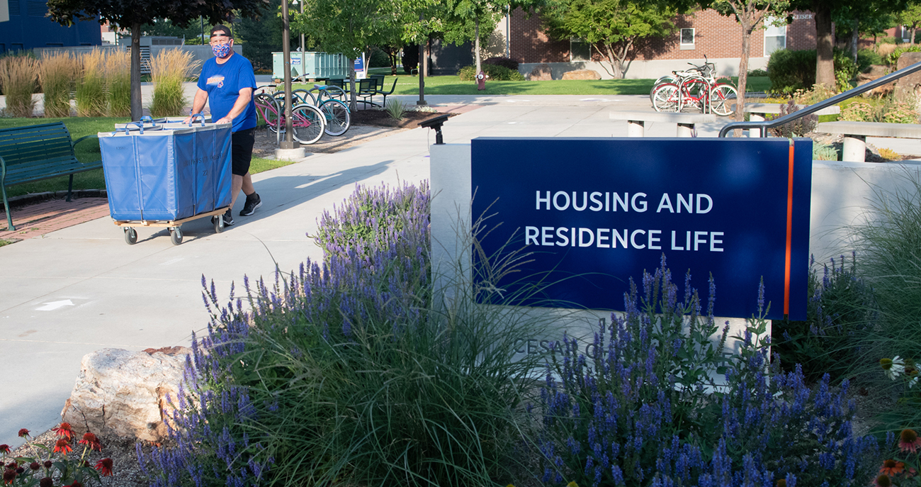 """Student walking by sign that says """"Housing and Residence Life"""""""