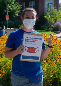 "Masked woman holding sign that reads ""facial coverings required on campus"""