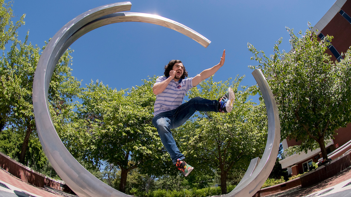 Student jumping through Boise State's circular sculpture